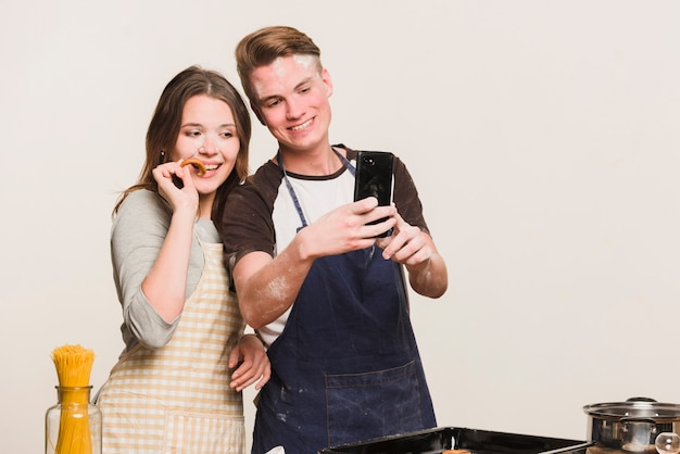 Amores haciendo fotos en la cocina Foto gratis