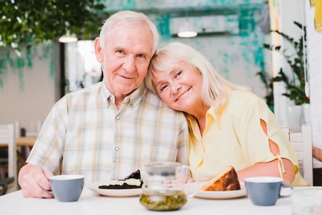 Amorosa pareja de ancianos bebiendo té y comiendo pastel Foto gratis