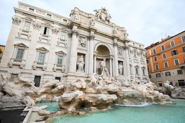 Amplio ángulo de visión de la famosa fontana de trevi. un lugar turístico popular en el centro de la ciudad. Foto Premium