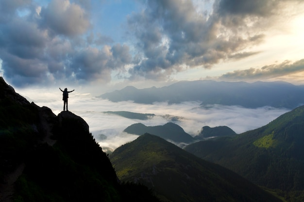 Amplio panorama de montaña. pequeña silueta de turista con mochila en montaña rocosa. Foto Premium