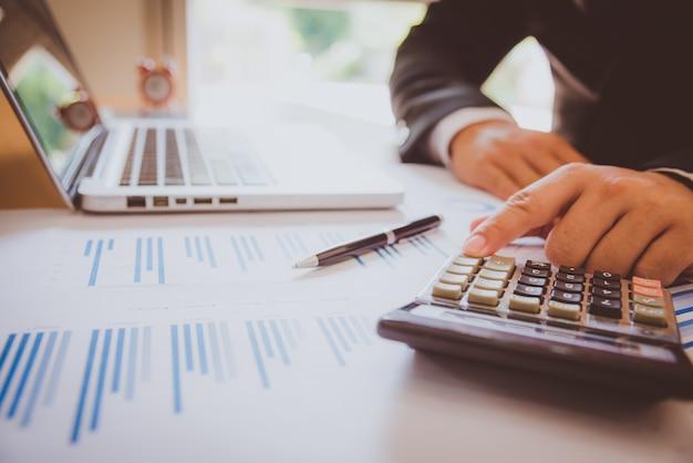Análisis de negocios - calculadora, hoja, gráficos y analista de la mano Foto Premium