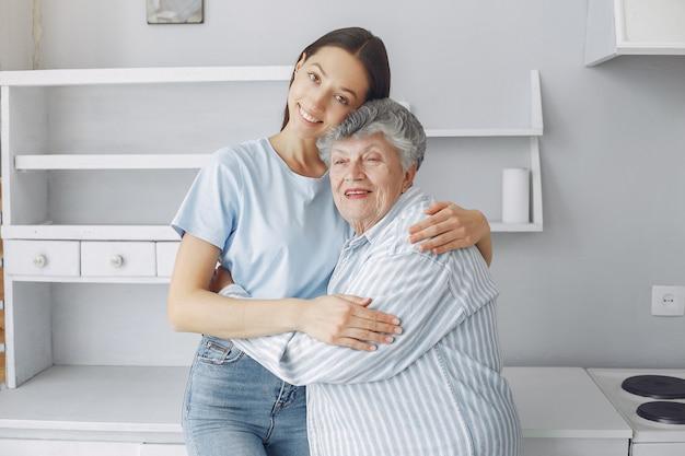 Anciana en una cocina con nieta joven Foto gratis