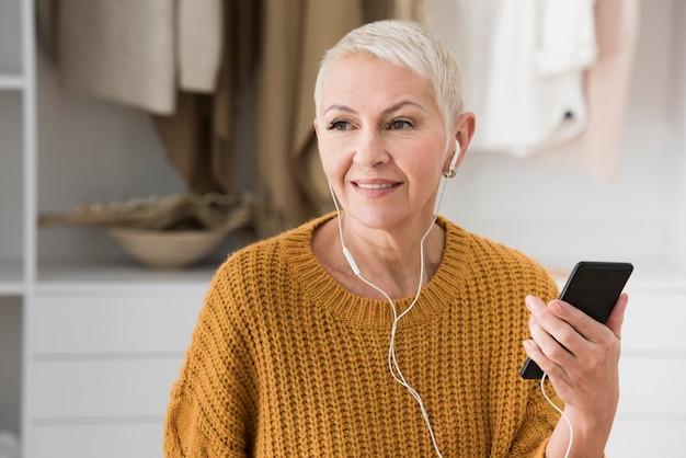 Anciana escuchando música con auriculares y sosteniendo smartphone Foto gratis
