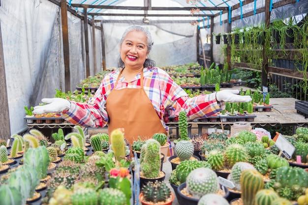 Anciana feliz con una granja de cactus Foto gratis