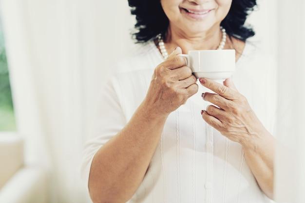 Anciana irreconocible con taza de té en casa Foto gratis