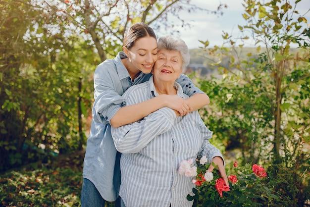Anciana en un jardín con joven nieta Foto gratis