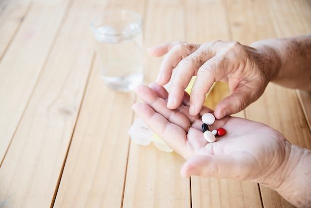 Anciana prepararse para comer píldora de medicina diaria Foto gratis
