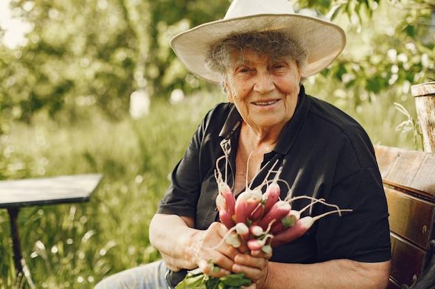 Anciana con sombrero sosteniendo rábanos frescos Foto gratis