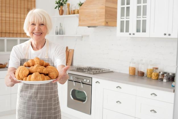 Anciana sosteniendo un plato con croissants Foto gratis