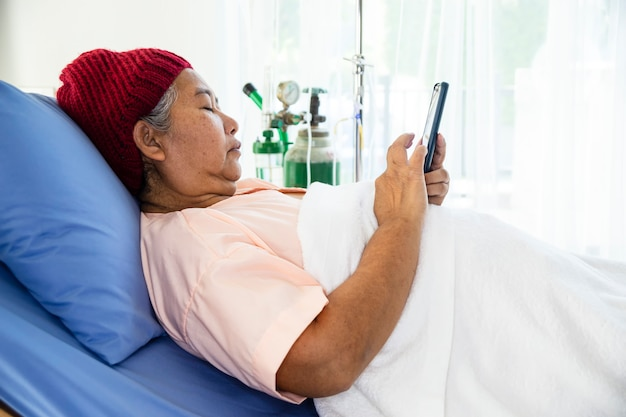 Anciana utiliza smartphone en la cama del paciente en el hospital Foto gratis