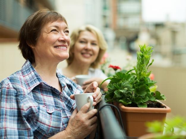 Ancianas en el balcón con café Foto gratis