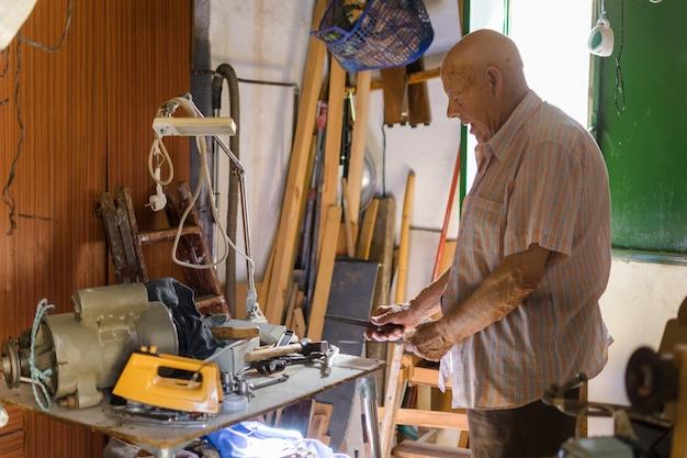 Anciano afilando un cuchillo con una lima Foto Premium