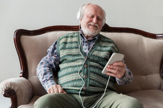Anciano de alto ángulo en el sofá tocando música en el móvil Foto gratis