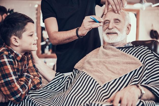 Anciano con niño en la barbería juntos. Foto Premium