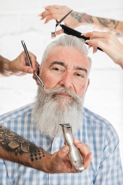 Anciano recibiendo peluquería y barba Foto gratis