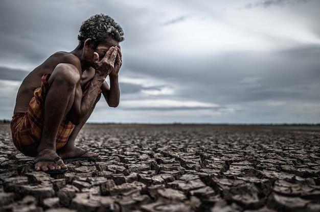 Un anciano se sentó con las rodillas dobladas en el suelo seco y las manos cerradas sobre su rostro, el calentamiento global Foto gratis