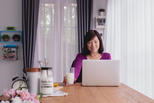 Ancianos asiáticos usando laptop y bebiendo leche en casa. Foto Premium