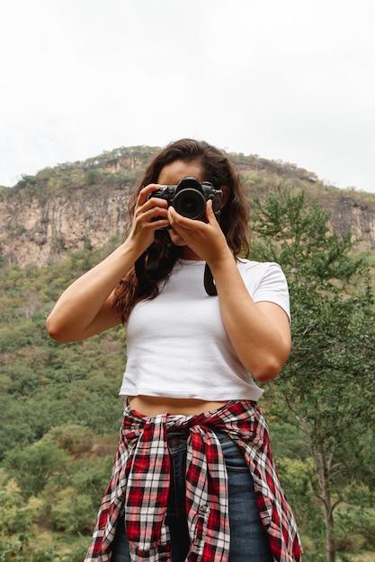 Ángulo bajo femenino sorprendente naturaleza en cámara Foto gratis
