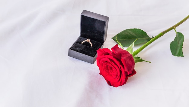 Anillo de boda con rosa en mesa blanca Foto gratis