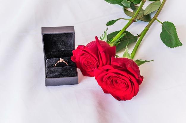 312cdd5e733b Anillo de boda con rosas rojas en mesa blanca. Foto gratis