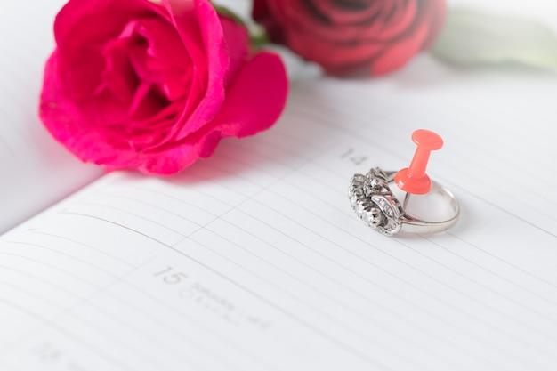 Anillo de diamantes en el libro de calendario con rosa rosa, el amor ...