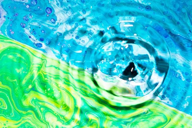 Anillos de agua de primer plano sobre fondo verde y azul Foto gratis