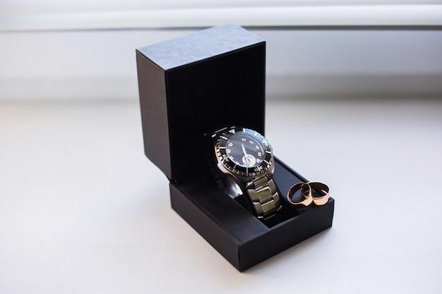 Anillos de boda en una caja de relojes, relojes de pulsera, relojes de bolsillo, hora, signo infinito de los anillos, anillos de boda Foto Premium