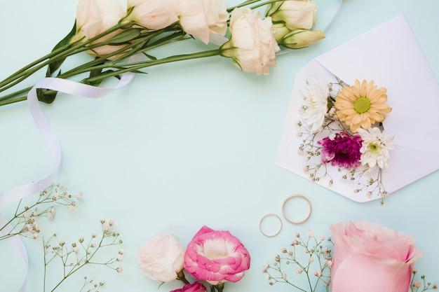 1c0c71352925 Anillos de boda y decoración de flores sobre fondo azul pastel ...