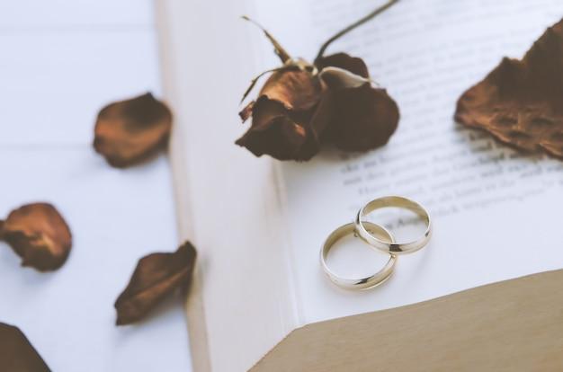 Anillos de boda de pareja con rosas secas en el libro abierto ...