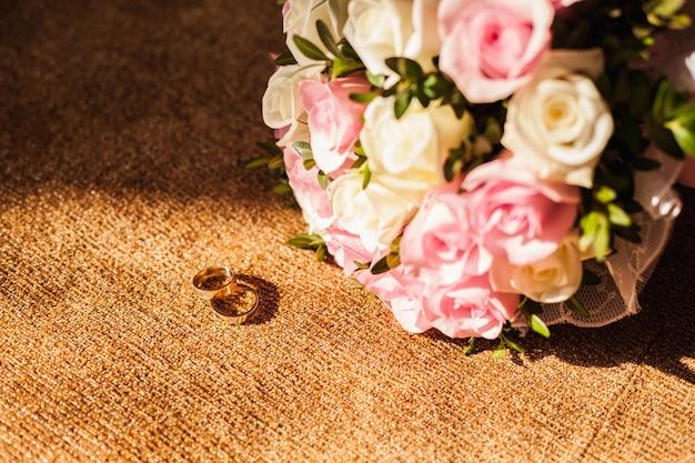 Anillos de boda con ramo de rosas rosadas Foto gratis