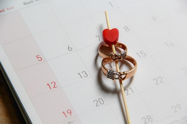 99bfbcc74350 Anillos de bodas en el calendario Foto Premium