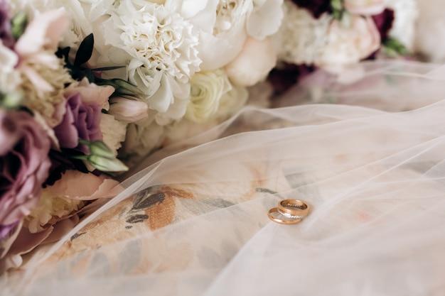 Los anillos de bodas del novio y la novia están en el velo de novia Foto gratis
