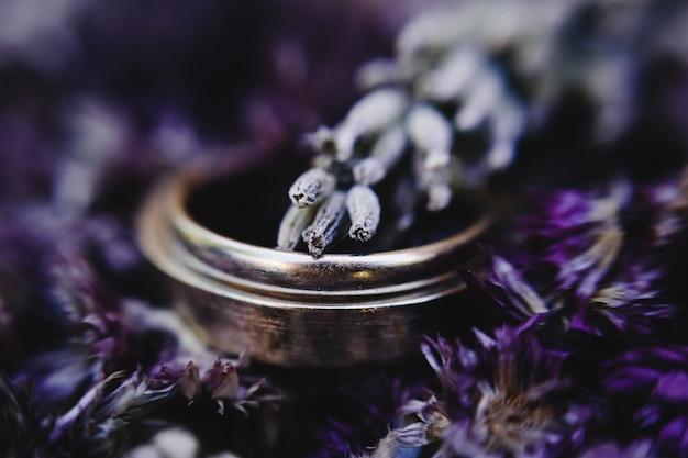 Anillos de bodas de oro se encuentran en el ramo de lavanda violeta Foto gratis