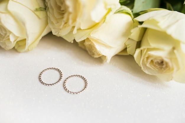 de83f7fde68a Anillos de bodas de oro y rosas frescas en el fondo blanco ...