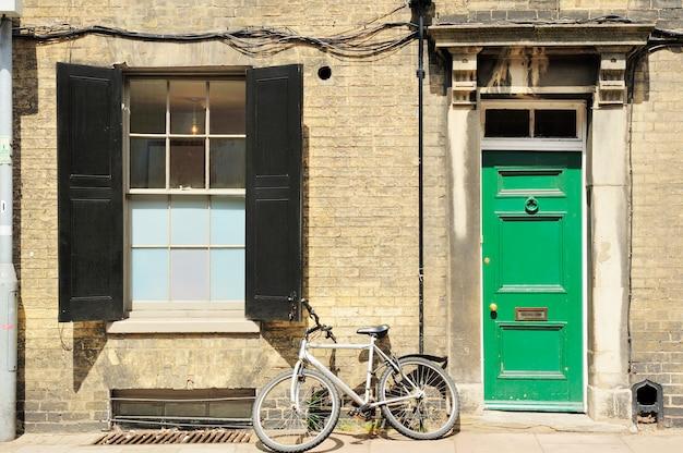 Antigua bicicleta clásica inclinada por la casa con puertas coloridas en inglaterra. Foto Premium