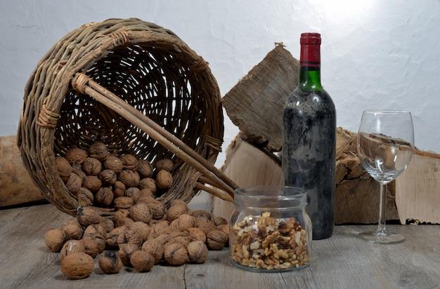 Antigua botella de vino con una cesta de nueces Foto Premium