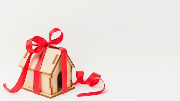 Antigua casa en miniatura con cinta roja sobre papel pintado blanco Foto gratis