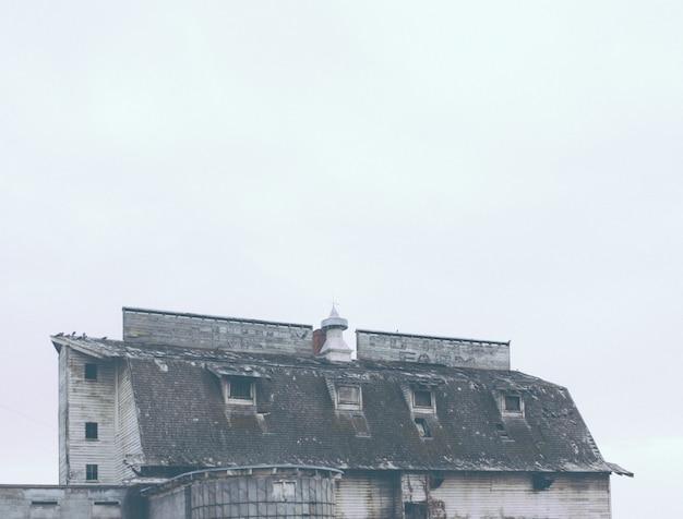 Antigua granja abandonada con un nombre de empresa sucio apenas visible en el techo Foto gratis