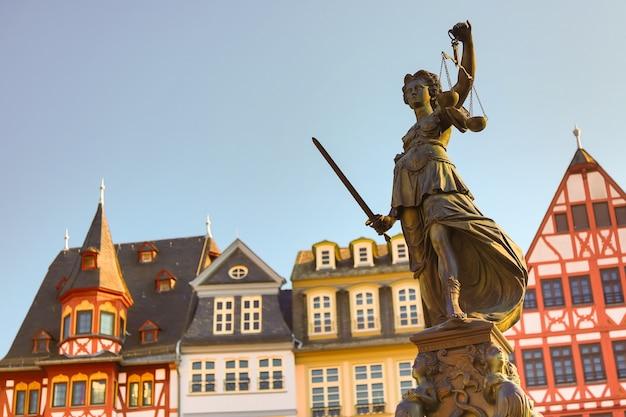 Antigua plaza de la ciudad de romerberg con la estatua de justitia en frankfurt main, alemania con cielo despejado Foto Premium