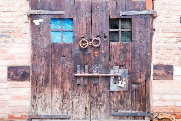 Antigua puerta doble de madera antigua con cerraduras antiguas y una manija en las calles de bérgamo, italia Foto Premium