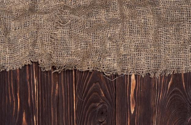 Antigua servilleta de tela de arpillera sobre fondo de madera marrón, vista superior Foto Premium