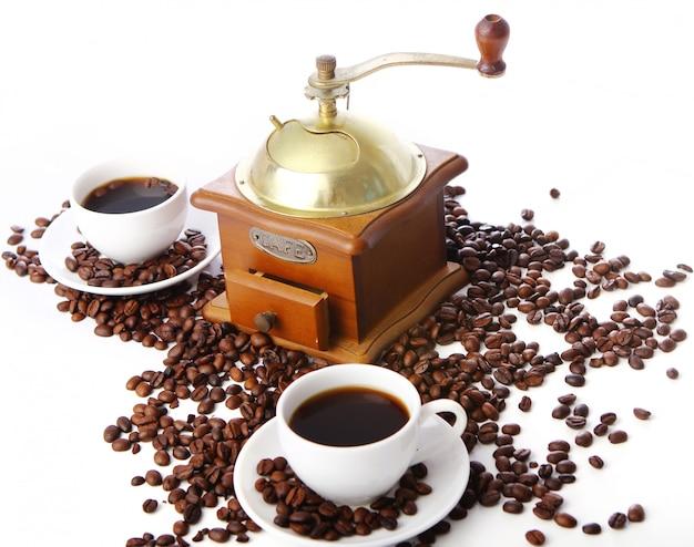 Antiguo molinillo de café con taza blanca Foto gratis