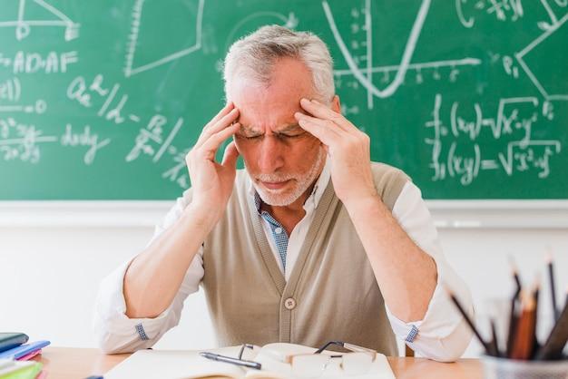 Antiguo tutor con dolor de cabeza en sala de lectura. Foto gratis