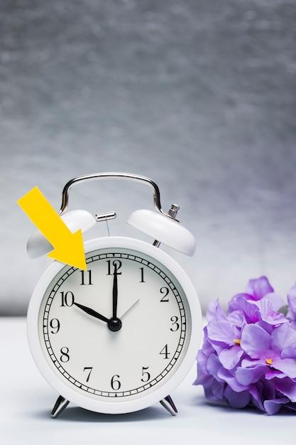 Anuncio de primavera en el reloj con flores al lado Foto gratis