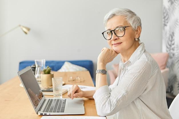 Aparatos electrónicos modernos, concepto de ocupación, edad y madurez. vista lateral de la atractiva mujer autónoma de mediana edad con estilo en gafas sentado frente a la computadora portátil abierta, trabajando en la oficina en casa Foto gratis