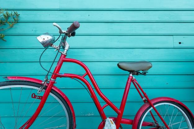 Aparcamiento bicyle rojo vintage en pared de madera azul Foto Premium