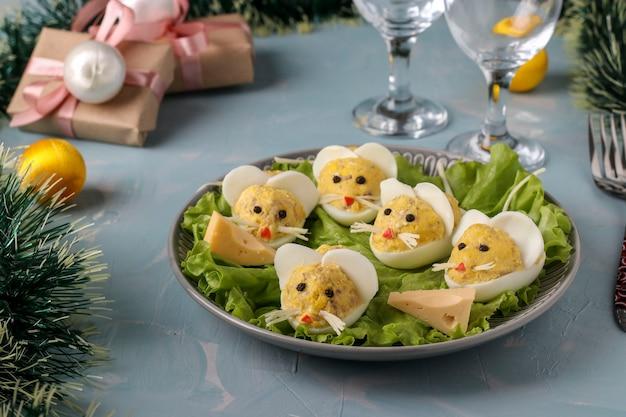 Aperitivo festivo ratones hechos de huevos rellenos con hígado de bacalao sobre un fondo azul claro Foto Premium