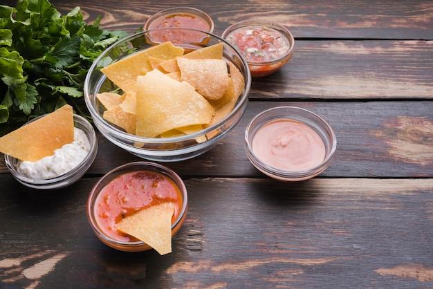 Aperitivo de nachos con salsas en mesa. Foto gratis
