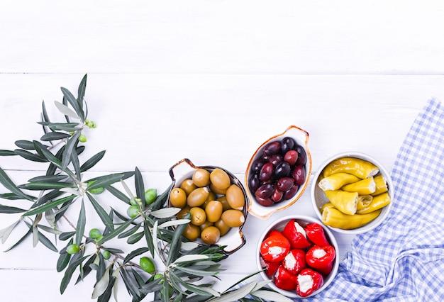 Aperitivos tradicionales, aceitunas verdes y rojas de la cocina griega. ramas frescas de aceitunas. copyspace encima. mantel a cuadros azul Foto Premium
