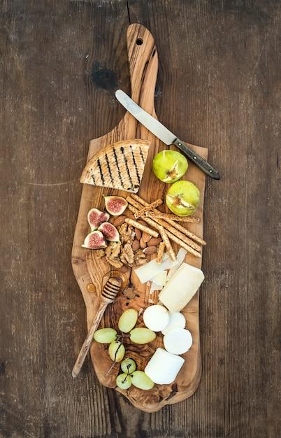Aperitivos de vino en tablero de madera de olivo sobre fondo rústico Foto Premium